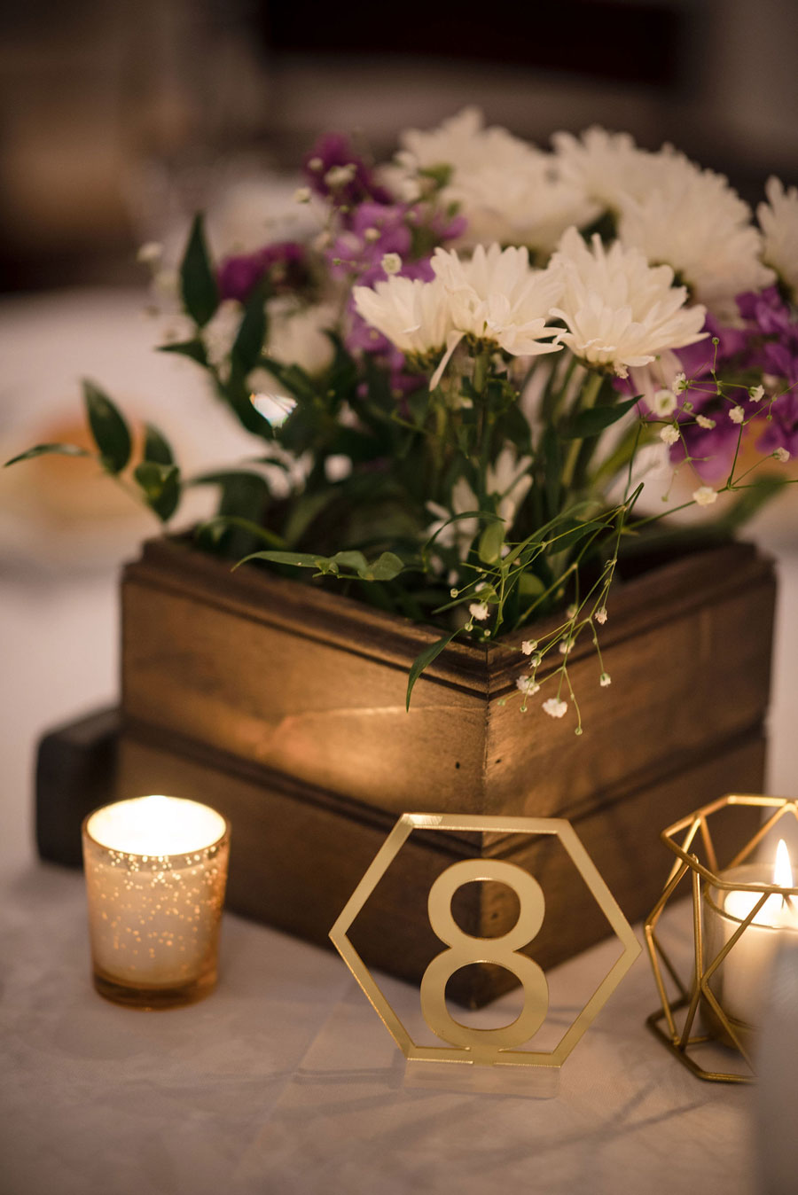 Brushed metal table numbers with floral arrangements